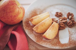 apple is sliced into wedges with cinnamon.