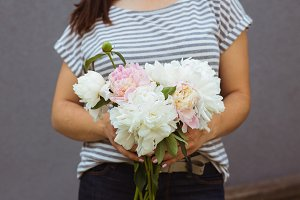 Girl with pink and white peonies bouquet