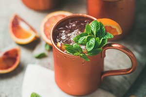 Blood orange Moscow mule alcohol cocktails in mugs on board