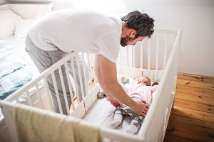 Father putting a sleeping toddler girl into cot at home.
