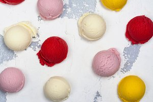 Orange, vanilla, raspberry and strawberry ice cream scoops on white background