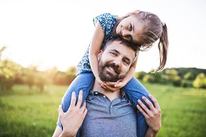 Father giving small daughter a piggyback ride in spring nature.
