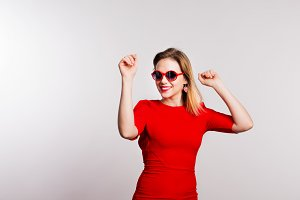 Portrait of a young beautiful woman with red sunglasses in studio.
