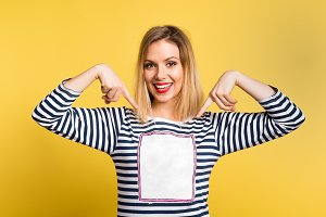 Portrait of a young beautiful woman in studio, copy space on her T-shirt. Yellow background.