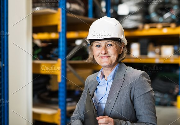 Senior Woman Warehouse Manager Or Supervisor With White Helmet And Clipboard