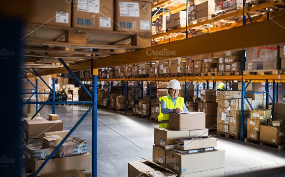 A Senior Woman Warehouse Worker Or Supervisor Controlling Stock
