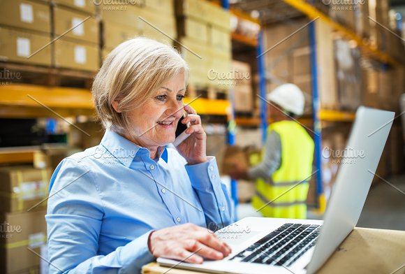 Senior Woman Manager With Smartphone And Man Worker Working In A Warehouse