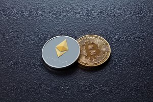 Two coins of crypto currency ETH, BTC on a black concrete background. Business, finance and technology concept.