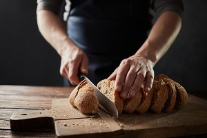 Male hands slicing home-made bread on the wooden board