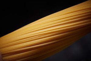 Macro photo of a yellow spaghetti on a black background