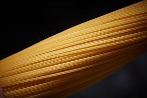 Macro photo of a yellow spaghetti on a black background
