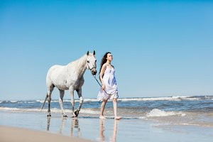 Girl and a horse walking on the beach.