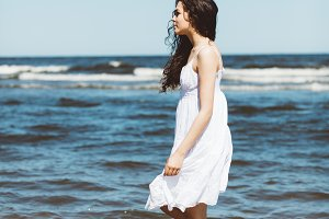 A girl in white dress walking alongside the ocean.