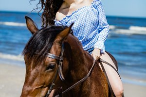 Young attractive girl sitting on a bay horse by the sea