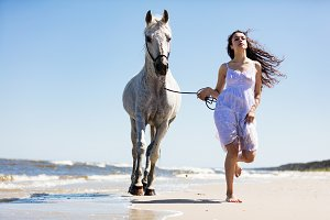 Young woman witth white horse running on the beach