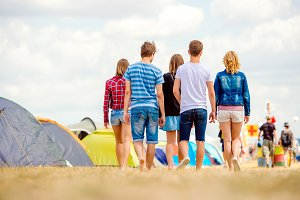 Unrecognizable teenagers, tent music festival, sunny summer, bac
