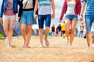 Unrecognizable teenagers, tent music festival, sunny summer, leg