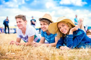 Teenagers at summer music festival, lying on the ground