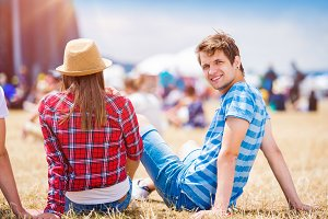 Teenage couple at summer music festival, sitting in front of sta