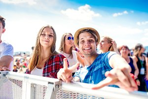 Teenagers at summer music festival, boy showing peace sign
