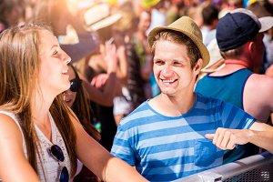 Teenage couple at summer music festival enjoying themselves