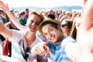 Teenagers at summer music festival in crowd taking selfie