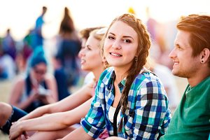 Teenagers at summer music festival, sitting on the ground