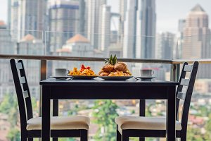 Breakfast table with coffee fruit and bread croisant on a balcony against the backdrop of the big city