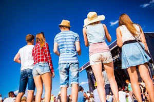 Teenagers, summer music festival, standing in front of stage