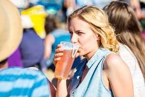 Young blond woman with beer at summer music festival