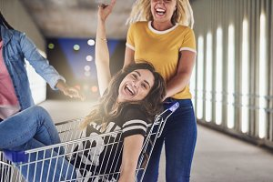 Laughing girlfriends playing with a shopping cart at night