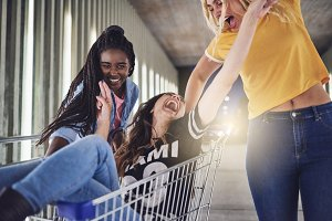 Young female friends pushing each other in a shopping cart