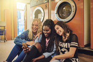 Laughing young women sitting at the laundromat using a cellphone