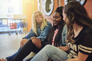 Laughing young women hanging out together on a laundromat floor