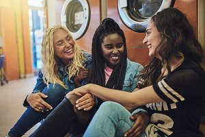 Diverse young girlfriends sitting together on a laundromat floor laughing