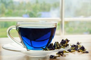 Cup of blue tea on wooden table.