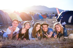 Teenagers lying on the ground in front of tents