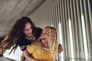 Laughing young woman carrying her girlfriend on her back
