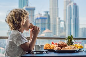 The boy is having breakfast on the balcony. Breakfast table with coffee fruit and bread croisant on a balcony against the backdrop of the big city
