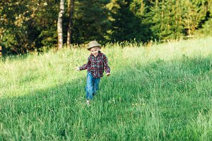 child boy running on meadow
