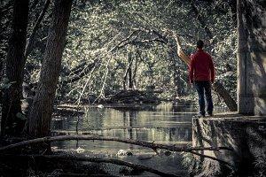 Man in dark park with pond