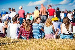 Teenagers at summer music festival, sitting on the grass