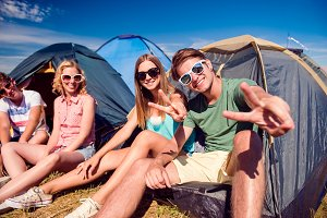 Teenagers sitting on the ground in front of tents