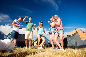 Group of teenagers at summer music festival dancing, tents