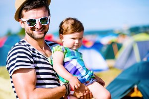 Young father with his baby daughter between tents, summer