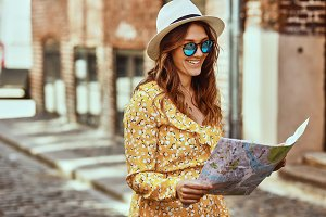 Smiling young woman reading a map while exploring cobblestone streets