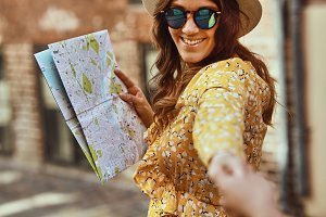 Smiling woman holding a map leading someone through the city