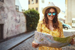 Smiling woman holding a map while exploring cobblestone city streets