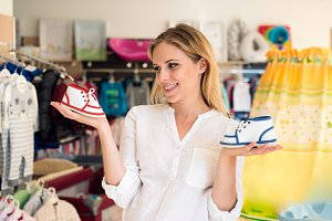 Pregnant woman shopping shoes for her baby