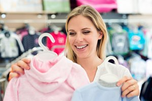 Pregnant woman shopping clothes for her baby